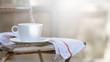 canvas print picture - weiße Kaffeetasse auf altem Gartenstuhl. Daneben ein altes Tuch. Vor hellem Hintergund. Geringe Schärfentiefe, selektive Schärfe. Die Sonne wirft leichte Schatten von Bäumen.