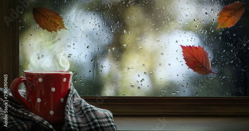 Photo  Autumn season background, red cup with hot drink and wet autumnal window