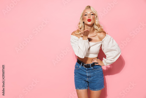 Fotografie, Obraz Image of glamour blonde woman with long curly hair wearing trendy clothes blowin