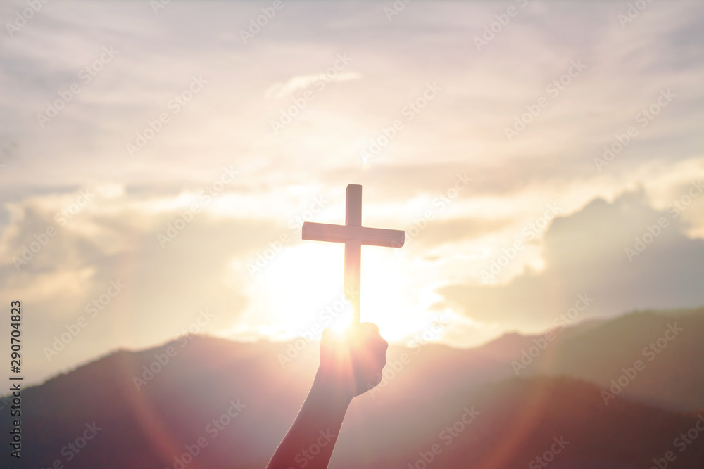 Fototapeta human hands praying to the GOD while holding a crucifix symbol with bright sunbeam on the sky