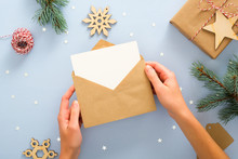 Female Hands Holding Empty Blank Card In Kraft Paper Envelope On Pastel Blue Background Decorated With Confetti, Gift Box, Fir Tree Branches. Christmas, New Year, Winter Holiday Invitation Mockup.