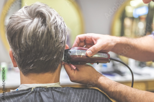 Fotografia  Barbershop. Hairdresser does hairstyle with hair clipper.