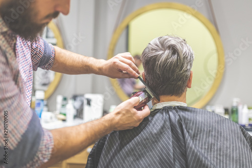 Stampa su Tela  Professional barber styling hair of his client by using comb and clipper