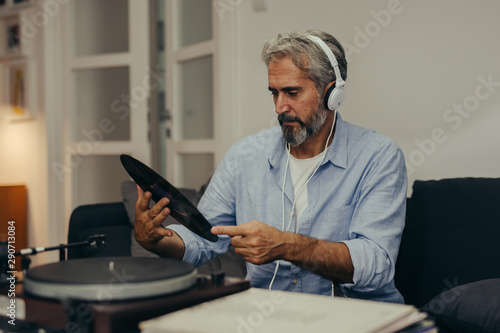 handsome middle aged man listening music on record player at his home - 290713084
