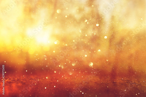 Foto  Abstract background of light burst among trees and glitter golden bokeh lights