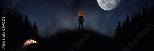Photo Halloween theme: scary maniac with pumpkin head in dark forest on sky background with midnight moon