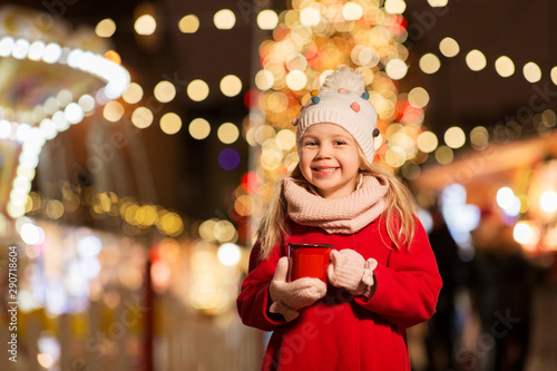 Photo sur Aluminium Chocolat holidays, childhood and people concept - happy little girl with cup of tea at christmas market in winter evening