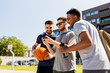 canvas print picture - sport, leisure games and male friendship concept - group of men or friends with smartphone at outdoor basketball playground
