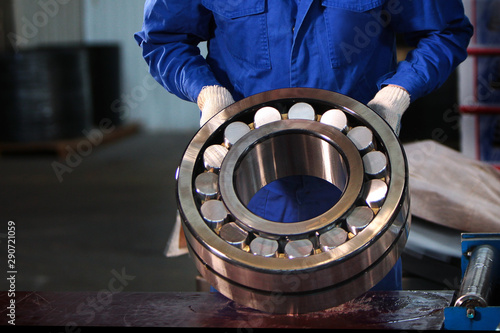 Fotomural  The finished bearing is in the hands of a worker at the factory
