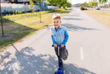Childhood, Leisure And Fun Concept - Happy Little Boy Riding Scooter In City