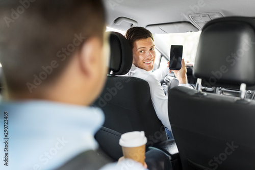 transportation, vehicle and technology concept - smiling car driver showing smartphone to male passenger