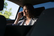 Smiling businesswoman using smart phone in the car
