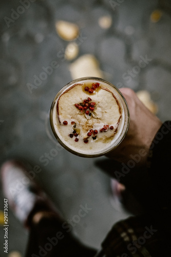 Fall hot punch cocktail in a man's hand, overhead. Autumn winter warming drink. Drink photography concept. Close up