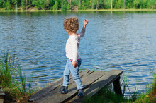 Little Girl Child With Curls Stands On The Shore Of A Forest Lake On A Wooden Pier And Throws Stones Into The Water In Summer Day.