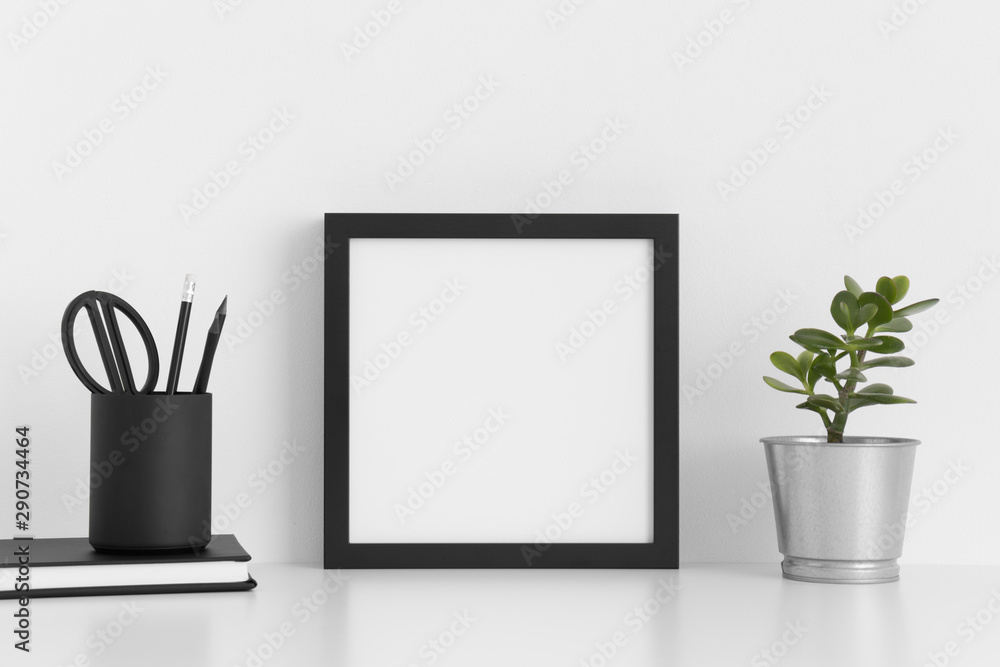 Fototapeta Black square frame mockup with a crassula in a pot and workspace accessories on a white table.