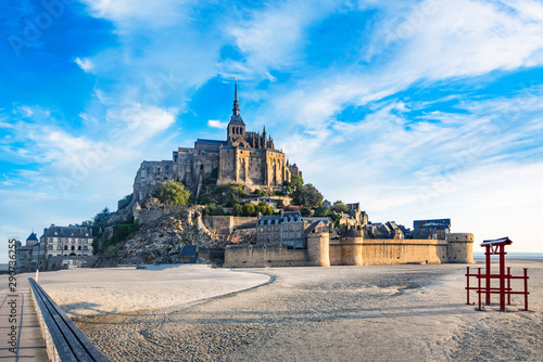 Dawn in Mont Saint Michel and its abbey with the sea at low tide