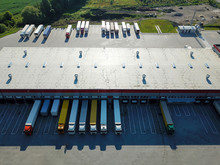 Aerial View Of Goods Warehouse. Logistics Center In Industrial City Zone From Above. Aerial View Of Trucks Loading At Logistic Center. View From Drone.