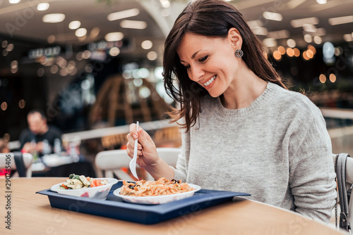 Papel de parede Portrait of a smiling woman eating lunch at food court.