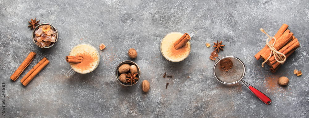 Fototapety, obrazy: Eggnog hot winter or autumn drink with milk, eggs and dark rum, sprinkled with cinnamon and nutmeg in cups on gray background, copy space, top view banner