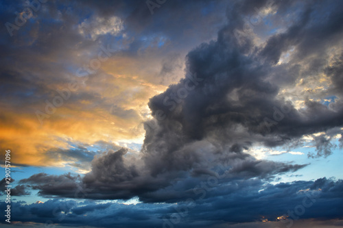 Obraz Storm clouds at sunset in orange and blue colors - fototapety do salonu