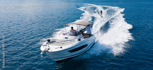 Fotografia  Speedboat with wakeboard rider on open sea