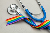 Fototapeta Tęcza - Stethoscope and LGBT rainbow ribbon pride symbol. Medical support after sex reassignment surgery. Grey background.