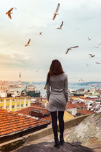 A Girl Stands On The Roof Of A House In Istanbul With Her Full Back Against The Backdrop Of A Beautiful Panorama Of The City With Flying Gulls.Young Woman Admires The Panorama Of Istanbul