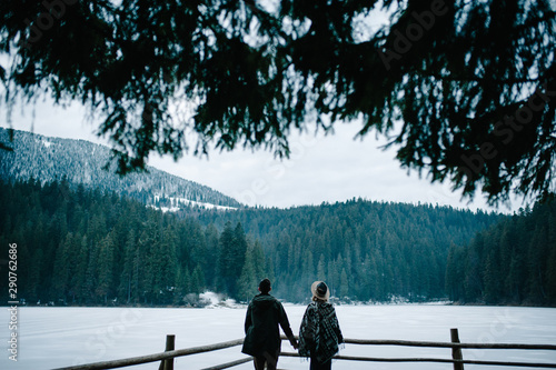 Foto auf AluDibond Blau türkis Young couple back standing on pier near the lake on nature. Winter lake against the background of the forest and the mountains. Landscape. Place for text and design. Close up.