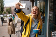 canvas print picture - Enchanting blonde young woman with smartphone take selfie on the street