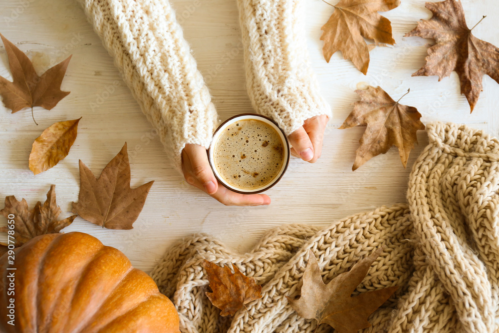 Fototapety, obrazy: Top view composition with young woman's hands in white sweater, vintage styled cup of coffee and autumn themed decoration, fallen leaves on textured background. Flat lay, copy space.