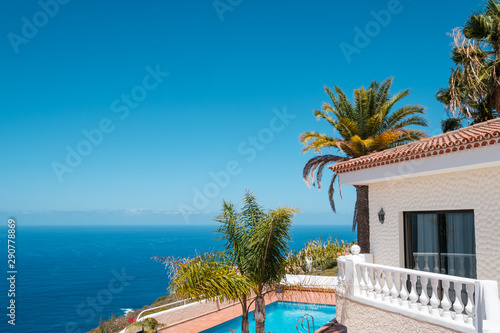Obraz na plátne  house with swimming pool, palm trees and ocean sea view