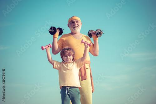 Portrait of senior man and cute child lifting dumbbells Wallpaper Mural