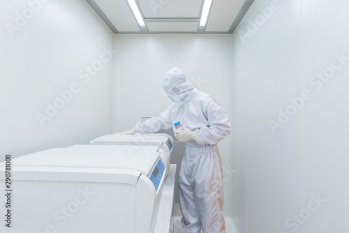 Fototapeta  A scientist in sterile coverall gown using Cleaning tool for cleaning laboratory