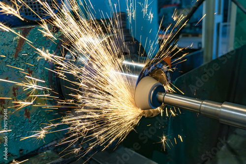 Obraz na plátně  Grinding operations with an end abrasive wheel on a circular grinding machine with sparks