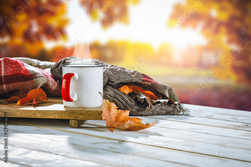 Poster Kamperen Autumn background with white wooden table board and mug on it. Blurred colourful trees view in distance.