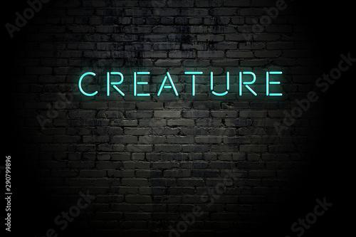 Obraz na plátně  Highlighted brick wall with neon inscription creature