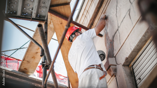 Fototapeta Man worker standing on scaffolding and restore old building facade obraz