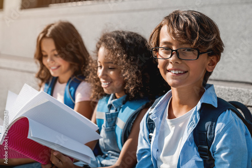 Portrait shot of cute little children with backpacks and notebooks outdoors. Boy smiling and looking at camera