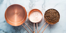 Copper Measuring Cups On Marble Table In The Kitchen. Ready To Cook Or Bulk Food Purchase Concept. Top View