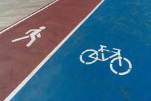 Blue Bicycle Lane Sign And Red Walking Lane Sign On Road.