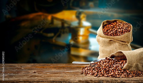 Salle de cafe Coffee beans in jute sacks with blurrred coffee machine view