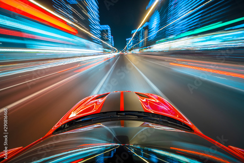 Fototapeta View from roof of the red muscle car Car moving in a night city, Blured road with lights with car on high speed. Concept rapid rhythm of a modern city. obraz