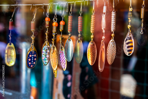 Fototapeta  Multicolored rotating lures hanging in the window of a fishing shop