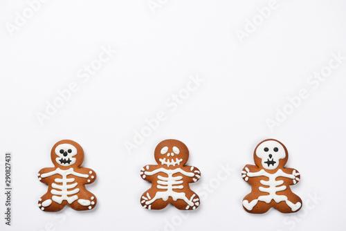 Fototapeta  The hand-made eatable gingerbread Halloween sceletons on white background