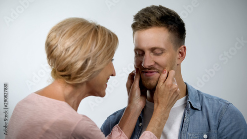 Mum pinching adult son cheeks, male smiling, overprotection effect concept Canvas Print