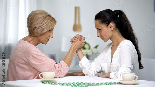 Fotografie, Obraz  Mother and daughter-in-law looking on each other during arm wrestling battle
