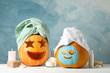 Leinwandbild Motiv Funny pumpkins and skin care accessories on white background, copy space