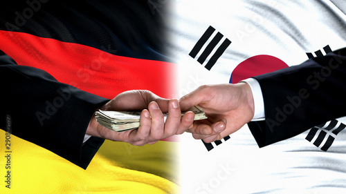 Germany and South Korea officials exchanging money, flag background, business Canvas Print