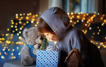 Christmas Mood. Cute Little Excited Child With Teddy Friend Looking Inside Gift Box With Christmas Toys And Light From It With Garland Lights Bokeh At Background At Home.
