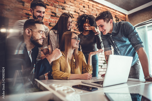 fototapeta na ścianę Team of six business people behind young businesswoman sitting and working on his laptop
